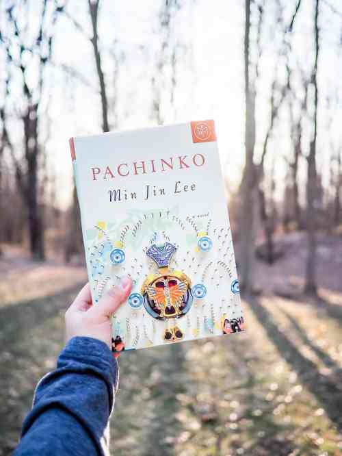 A hand holding the book Pachinko by author Min Jin Lee.