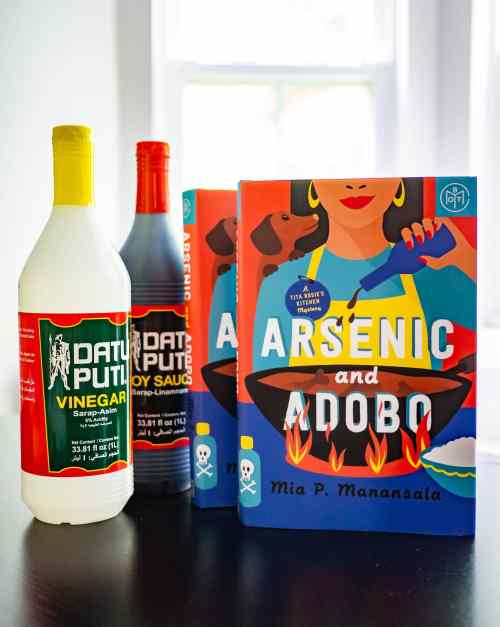 Two copies of the hardover edition of Arsenic and Adobo are standing on black surface next to a bottle of Datu Puti vinegar and Datu Puti soy sauce.
