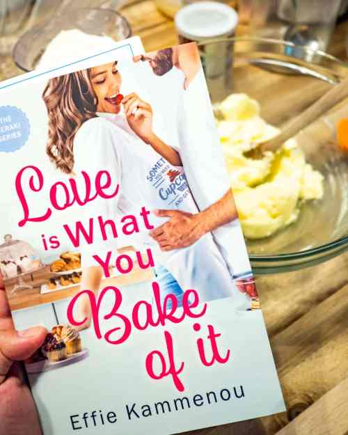 A hand holds the book Love is What You Bake of it. In the background you can make out a mixing bowl with batter.