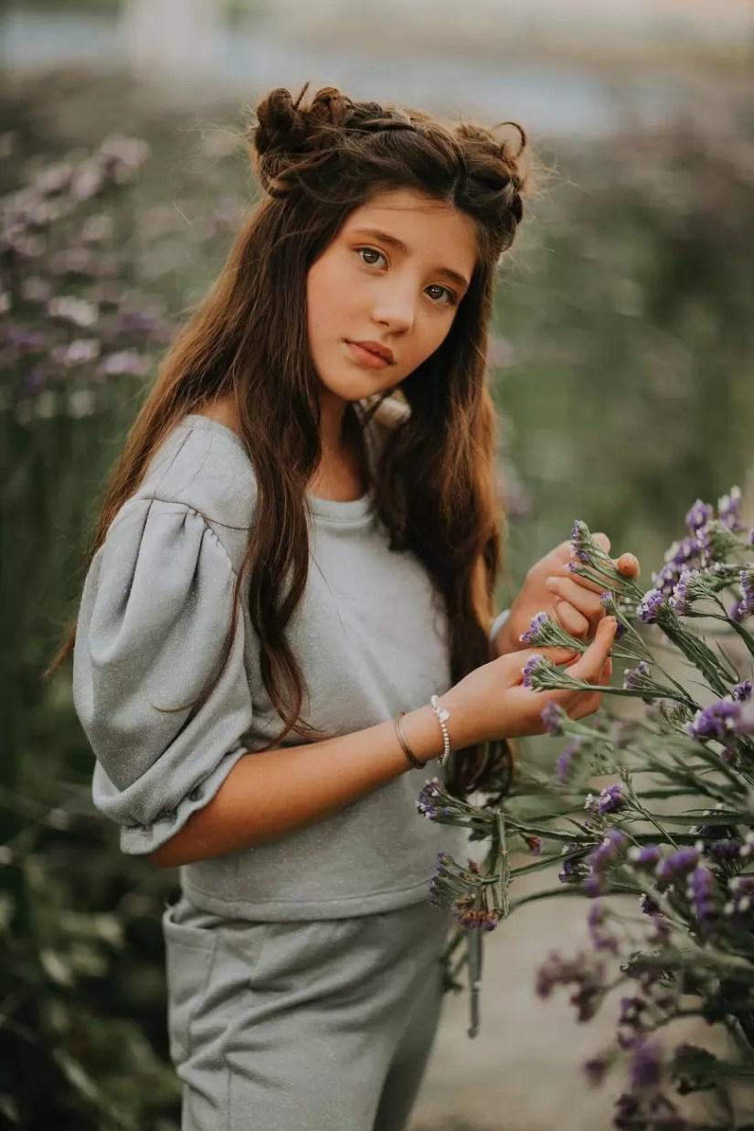tender teenage girl with long dark hair near blooming bush
