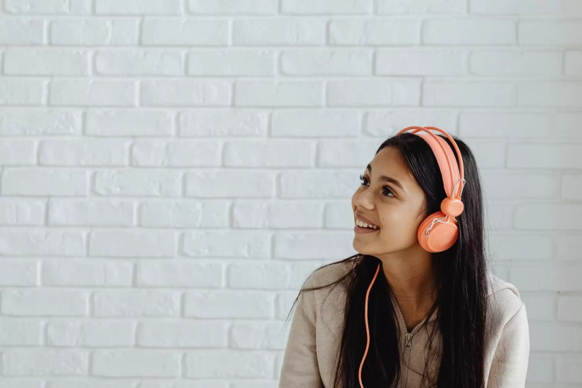 smiling female teenager listening to music