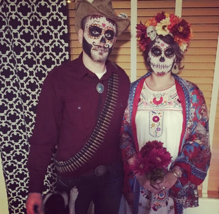 A couple dressed up in Dia de Los Muertos regalia.