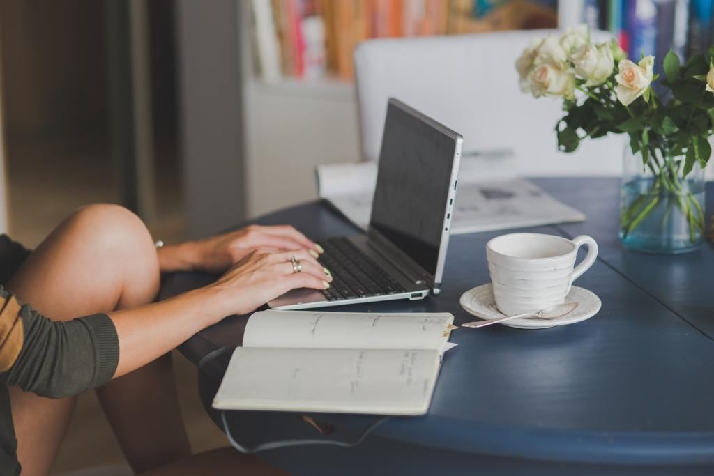 Women Typing On Her Computer at a Table with a Notebook and Cup of Coffee