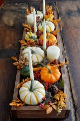 For this glorious DIY FALL TABLESCAPE, Louisville, Ky.-based design blogger Tricia Weldy (724southhouse.blogspot.com) started with a long wooden box and layered up: First she added layers of foam down the center so the pumpkins would stand higher than the foliage, then spread out one bag of Spanish moss across the top. She then spaced out an assortment of orange and white pumpkins and gourds, interspersing tall tapered candles and pillar candles between them (Weldy cut out holes in the foam to secure the candles in place) and trimmed and tucked pieces of craft-store stems of fall foliage, letting them spill over the edges.