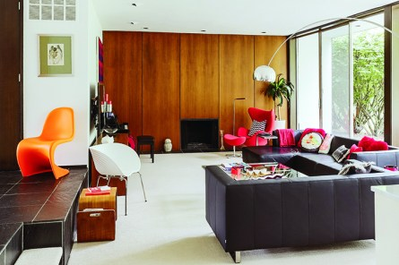 """""""We call it the Mad Men wall,"""" Hughet-Hiller says of the floor-to-ceiling walnut paneling in the sunken living room. She found the neatly formed sectional at BoConcept; the Arco floor lamp was picked up at an estate sale."""