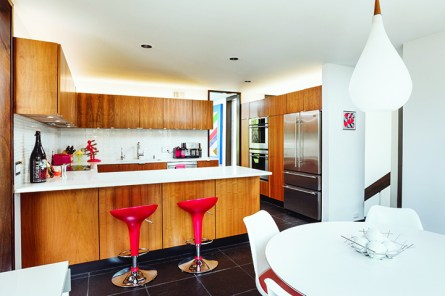 """Hughet-Hiller made the most changes in the kitchen. She replaced the original cabinets with IKEA base interiors, had a carpenter clad them in walnut, then topped them with Caesarstone quartz counters. The original Corian counters ran up the walls; Hughet-Hiller brought in Walker Zanger glass tile for the windowless backsplash. """"I wanted it super-reflective, so I can see behind me,"""" she says. The floating uppers were moved up six inches for function and to lend a feeling of height, then ribboned with LED lighting. Hughet-Hiller has had the Target bar stools since her first apartment."""
