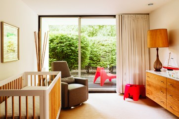 What is now the nursery for the couple's new baby originally had a pair of mounted twin headboards that matched the 8-foot-long white-laminate-topped oak dresser, which Hughet-Hiller kept. The toy red-plywood elephant was designed in 1945 by Charles and Ray Eames; Hughet-Hiller found it at Vitra. The eco-friendly crib is by Babyletto.