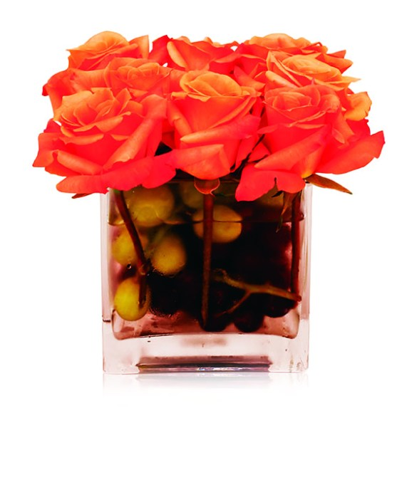 Create a simple arrangement (in a dollar-store square vessel) that discreetly nods to the season's palette with lush ORANGE ROSES — and the season's feast with OVERSIZE OLIVES in varying colors.