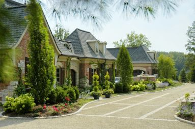 Chateau façade with French garden and crushed granite driveway.