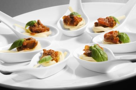 Miniature portions of spaghetti bolognese served as canapAs on chinese spoons with an oregano garnish