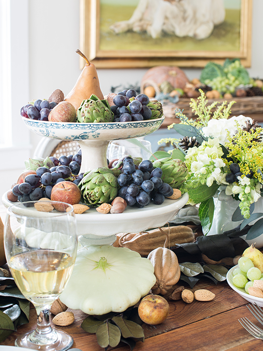 On this table, Marian Parsons creates a HARVEST BOUNTY by stacking mismatched (or matched, if you have them) pedestal cake plates or fruit bowls and fills them to overflowing with grapes, artichokes, pears and nuts for a seasonal, edible centerpiece.