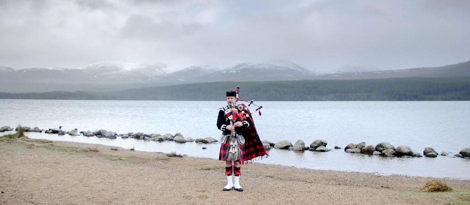 Scottish man playing bagpipe next to a loch