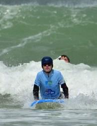 Un see surfeur qui pousse sur ses bras pour faire son take off avec en fond une vague qui déferle