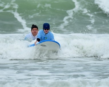Un bénévole qui fait surfer un see surfeur.