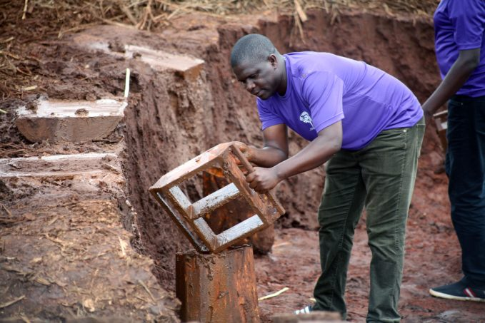Our Founding director Laying bricks at our school site in Luuka