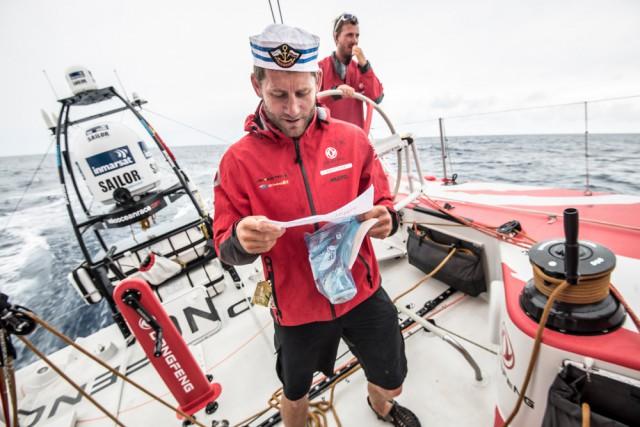 Charles Caudrelier liest seine Geburtstagspost und trägt den neuen Skipper-Hut. © Sam Greenfield / Dongfeng Race Team / Volvo Ocean Race