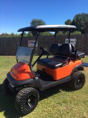 Orange lifted golf cart with custom wheels