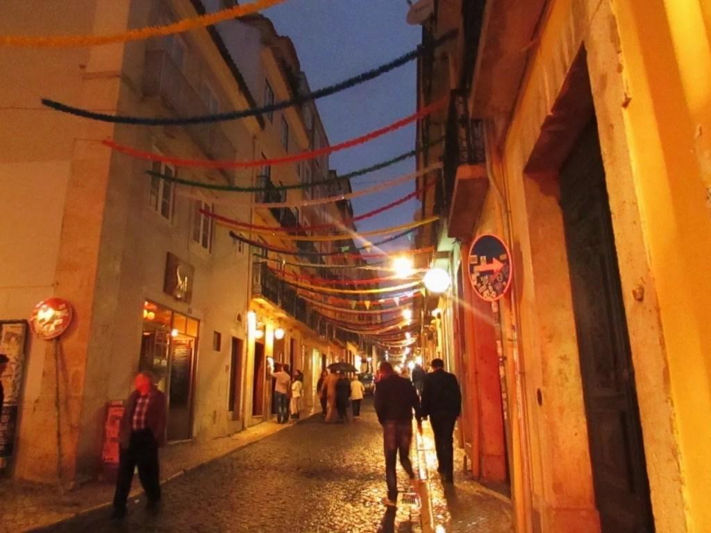 pequena rua com pendentes coloridos ligando os prédios de cada lado.