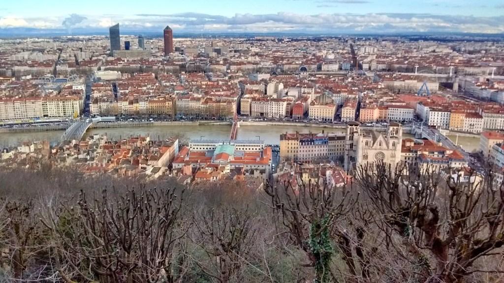 Lyon vista de cima da colina da Fourvière, uma cidade no horizonte, cortada por um rio no meio na horizontall, e com árvores secas na base da foto.