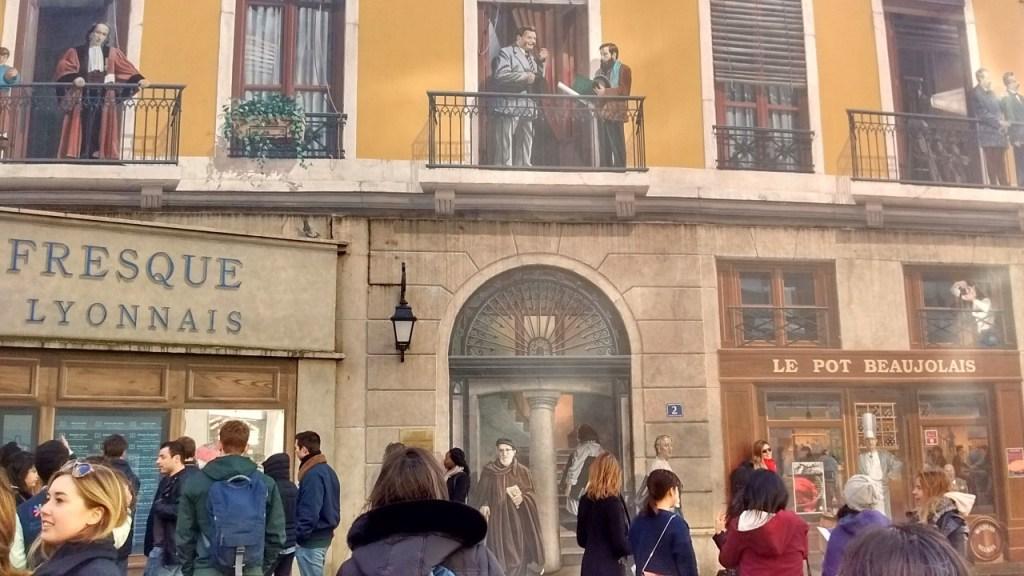 Pessoas e pinturas se misturam confundindo quem passa na frente da Fresque des Lyonnais Celèbres.
