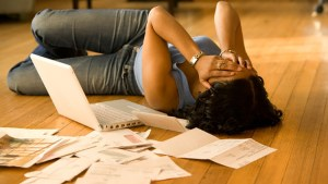 overwhelmed woman paying her bills - overwhelmed-woman-paying-her-bills