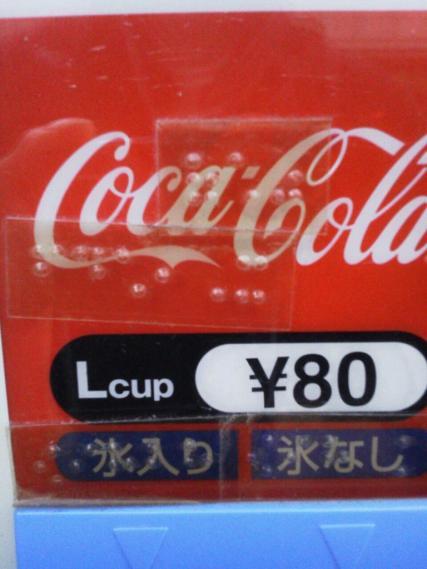 自動販売機に貼られた点字の写真。「みかん」と書かれてはいるが、実際に売られているのはコーラ。