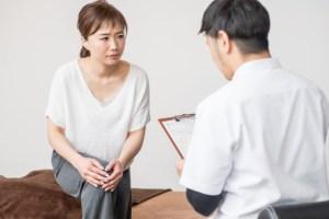 膝の痛みを医師に訴える女性