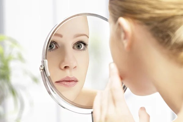 young beautiful healthy woman and reflection in the mirror