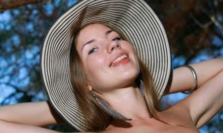 Jonge vrouw met hoed, naakt in de natuur