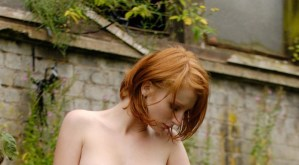 Clelia, mooi en rood haar, doet aan buiten naakt