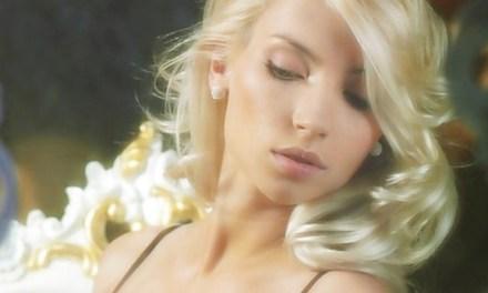 Adele B, lang blond krullend haar, doet een erotische striptease