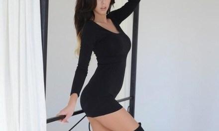 Jennifer Ann in een strak zwart jurkje en panty's