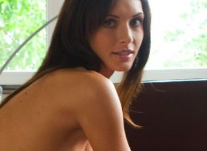 Klaudia, knappe brunette, heeft een erotische bui en zit naakt op de bank