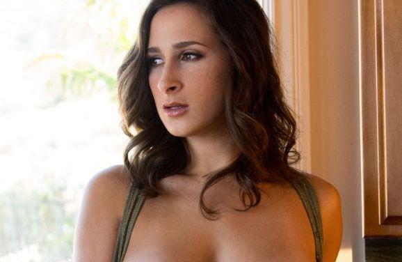 Knappe brunette met grote tieten, doet erotisch voor het huiskamerraam
