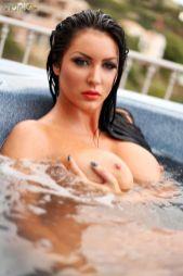 Donkerharige schoonheid, naakt in het zwembad