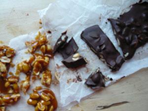 Rezept Topfenkuchen: Knuspriger Schoko-Erdnuss-Boden mit zweifarbiger Topfencreme, gespickt mit selbstgemachten Karamell- und Schokoerdnüssen.