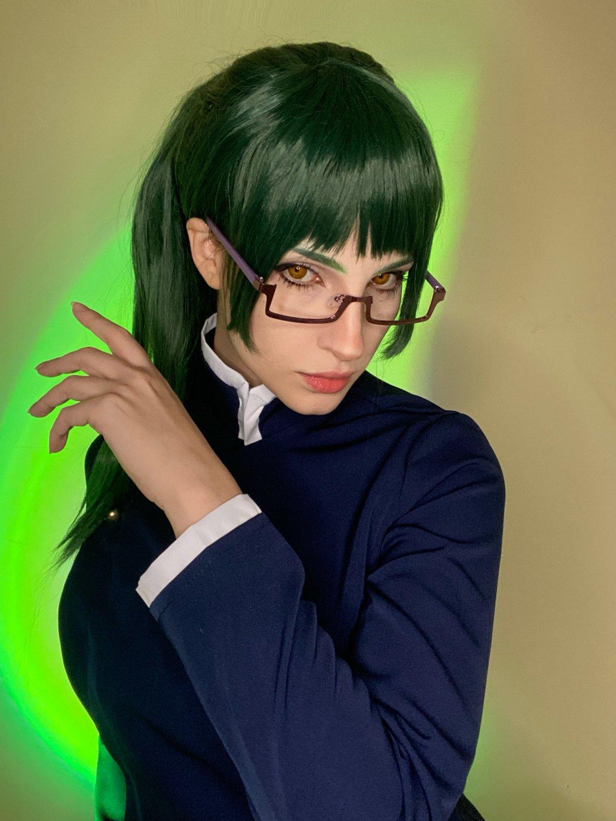 Cosplay da Maki Zenin, de Jujutsu Kaisen, da Samanta Bravin. O cosplay tem um vestido e a personagem tem cabelos verdes e óculos. A Samanta está olhando para a foto.