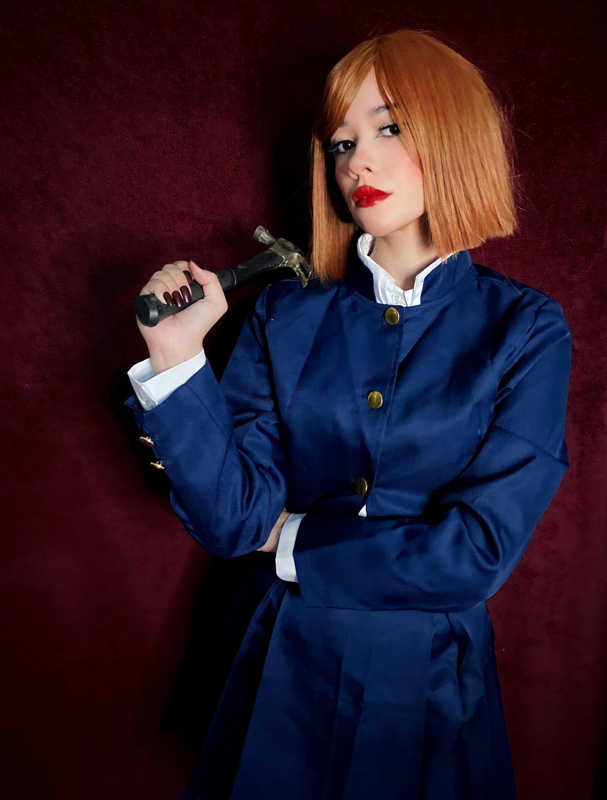 Belo cosplay da Nobara, de Jujutsu Kaisen, da cosplayer e streamer brasileira Carolina Lima. Na foto ela está segurando um martelo e a caracterização traz ela com um vestido.