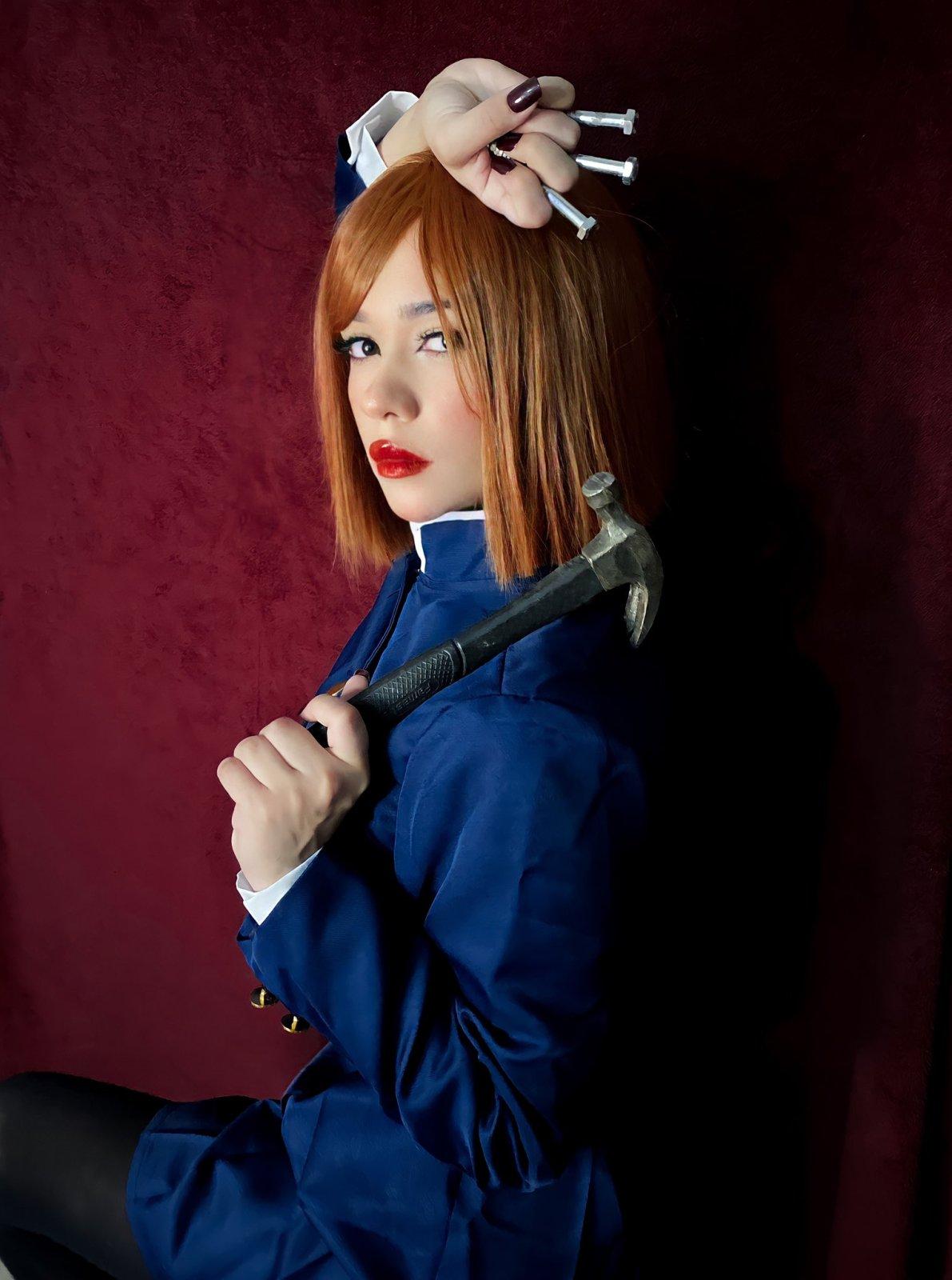 Belo cosplay da Nobara, de Jujutsu Kaisen, da cosplayer e streamer brasileira Carolina Lima. Na foto ela está segurando um martelo e pregos, e a caracterização traz ela com um vestido.