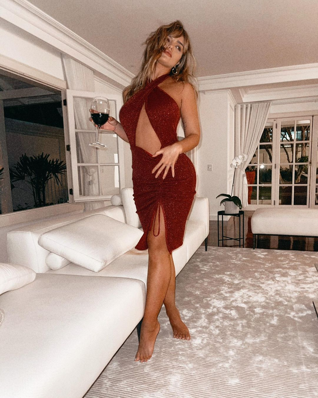 Rafa Kalimann está usando um belo vestido vermelho e segurando uma taça de vinho.