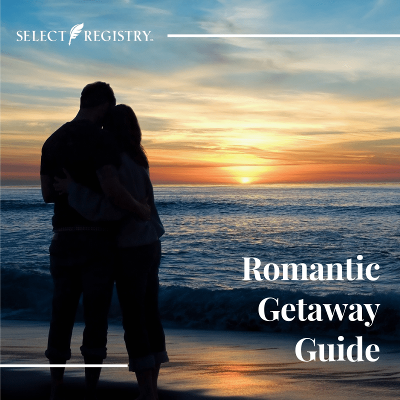 Access Our ROmantic Getaway Guide! Couple standing on the beach looking out over the sunset.