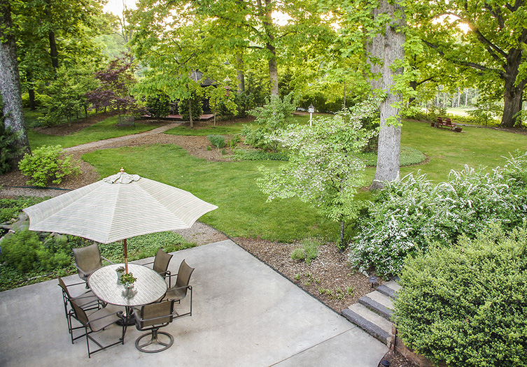 Looking down on grassy back yard, large trees, including patio with exterior table, cream colored umbrella and 6 chairs