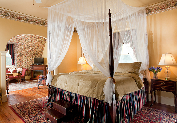 Devon suite with four poster canopy bed draped in white, nightstands, wood floors and area rug