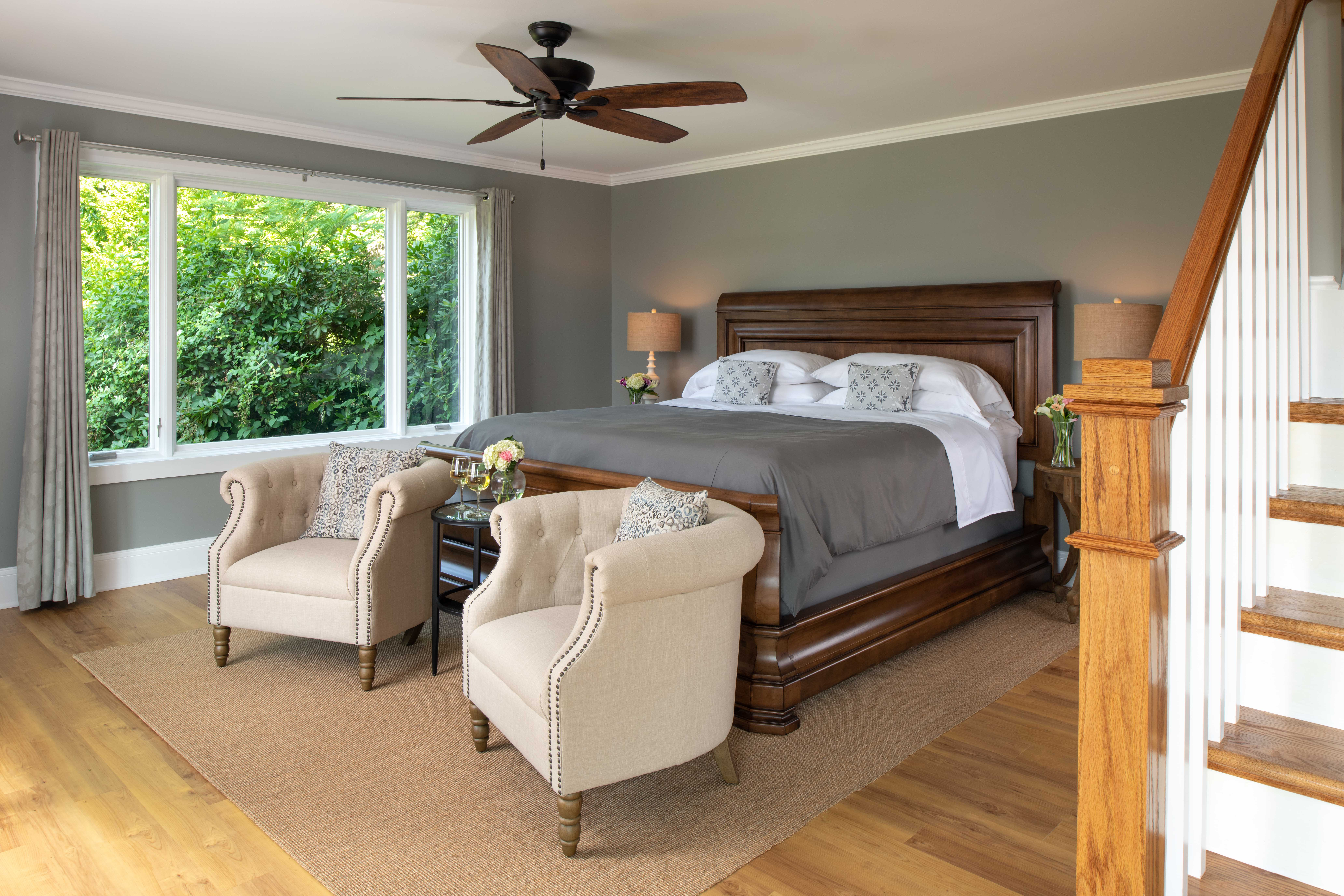 Arcady's Madison Suite with light hardwood floors, area rug, large bed, upholstered chairs and large window