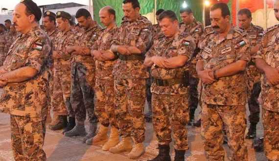 Jordan's King Abdullah joins top officers to perform night prayers during his visit at a northern borders guards unit at the Jordanian-Syrian border