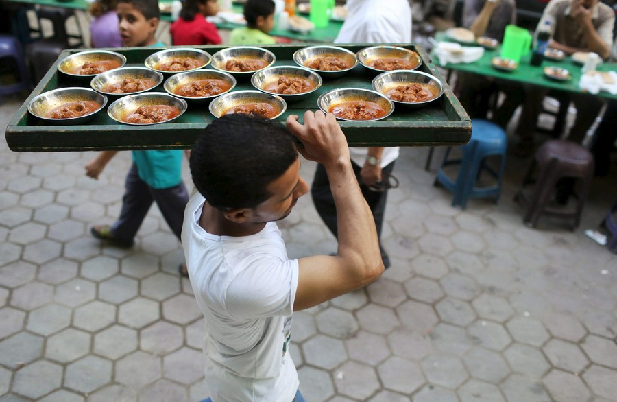 A volunteer carries food to tables as people wait to eat their Iftar meal during the holy fasting month of Ramadan in Cairo