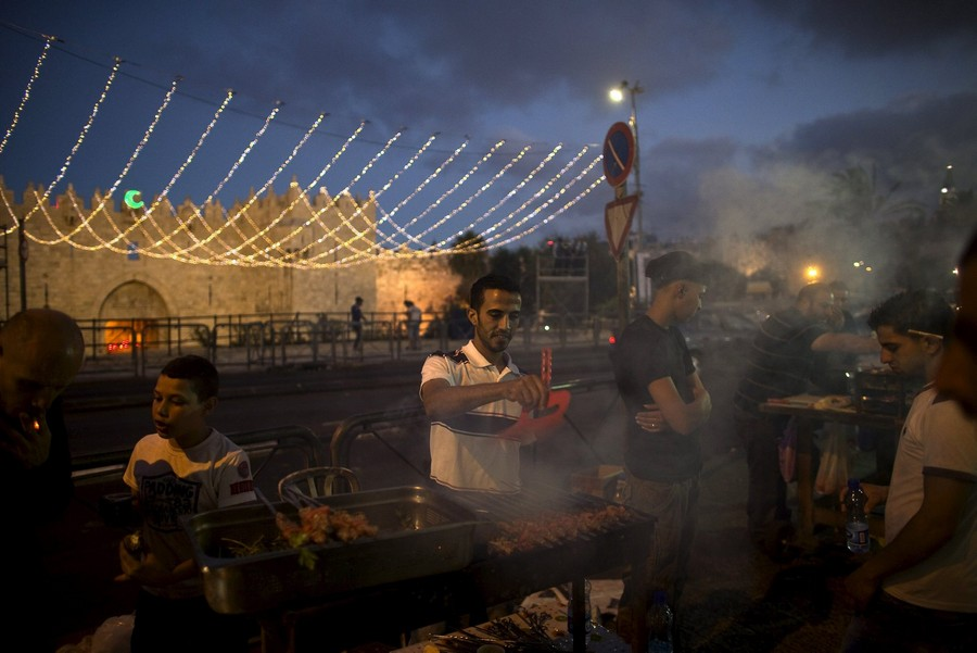 Palestinian vendors sell food at the end of Muslims' daily fast during the holy month of Ramadan outside Jerusalem's Old City