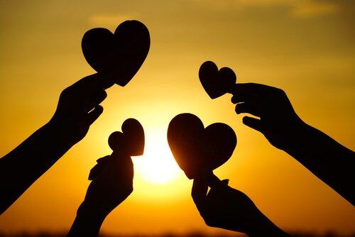 Cuatro-manos-sosteneniendo-corazones