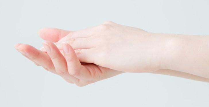 乾燥対策のクリームを手のひらで温めている女性の画像