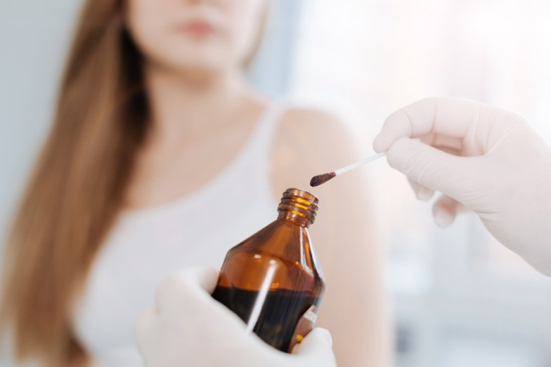 Using iodine for treatment. Concentrated motionless little patient sitting in the hospital and waiting for treatment while dermatologist holding the bottle of iodine